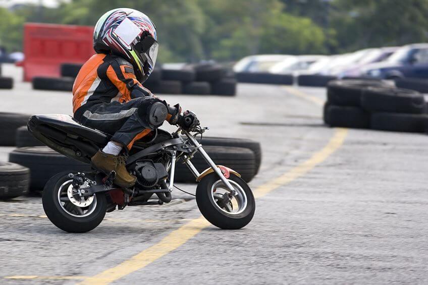 Niño montando en minimoto en circuito